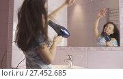 Купить «Beautiful happy girl teenager dries hair with hair dryer and sings and dances in front of a mirror in the bathroom stock footage video», видеоролик № 27452685, снято 14 января 2018 г. (c) Юлия Машкова / Фотобанк Лори