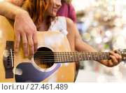 Купить «close up of couple playing guitar over lights», фото № 27461489, снято 11 декабря 2014 г. (c) Syda Productions / Фотобанк Лори