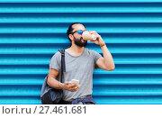 Купить «man with smartphone drinking coffee over wall», фото № 27461681, снято 2 июня 2016 г. (c) Syda Productions / Фотобанк Лори