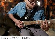 Купить «man playing guitar at studio or concert», фото № 27461685, снято 18 августа 2016 г. (c) Syda Productions / Фотобанк Лори