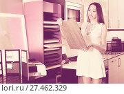 Купить «Pretty woman looking for modern stylish kitchen fronts», фото № 27462329, снято 15 июня 2017 г. (c) Яков Филимонов / Фотобанк Лори