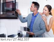 Купить «Smiling female choosing for new modern mini oven», фото № 27462337, снято 15 июня 2017 г. (c) Яков Филимонов / Фотобанк Лори