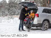 Отец наливает горячий чай ребенку, сидящему в багажнике автомобиля. Зимний заснеженный лес. Стоковое фото, фотограф Кекяляйнен Андрей / Фотобанк Лори