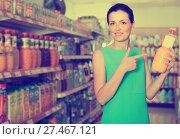 Купить «Female in the supermarket holding juice in bottle», фото № 27467121, снято 6 июня 2017 г. (c) Яков Филимонов / Фотобанк Лори