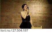 Купить «Красивая молодая певица с винтажным микрофоном на фоне кирпичной стены», видеоролик № 27504197, снято 24 января 2019 г. (c) Евгений Ткачёв / Фотобанк Лори
