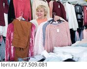 Купить «woman holding jumper, pants and jacket», фото № 27509081, снято 20 декабря 2017 г. (c) Яков Филимонов / Фотобанк Лори