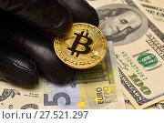 Купить «Рука в черной перчатке держит биткоин. Биткоин, доллары и евро», эксклюзивное фото № 27521297, снято 30 января 2018 г. (c) Юрий Морозов / Фотобанк Лори