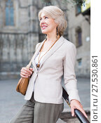 Купить «Cheerful mature female is walking in classic jacket», фото № 27530861, снято 3 сентября 2017 г. (c) Яков Филимонов / Фотобанк Лори