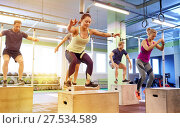 Купить «group of people doing box jumps exercise in gym», фото № 27534589, снято 19 февраля 2017 г. (c) Syda Productions / Фотобанк Лори