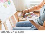 Купить «artist applying paint to palette at art studio», фото № 27534605, снято 1 июня 2017 г. (c) Syda Productions / Фотобанк Лори