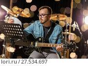 Купить «man playing guitar at studio rehearsal», фото № 27534697, снято 18 августа 2016 г. (c) Syda Productions / Фотобанк Лори