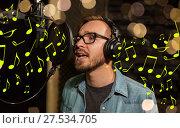 Купить «man with headphones singing at recording studio», фото № 27534705, снято 18 августа 2016 г. (c) Syda Productions / Фотобанк Лори