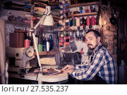 Купить «male worker sewing stitches on belt in leather workshop», фото № 27535237, снято 22 марта 2019 г. (c) Яков Филимонов / Фотобанк Лори