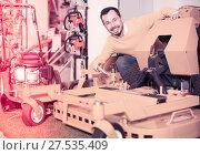 Купить «positive man deciding on best lawnmower in garden equipment shop», фото № 27535409, снято 2 марта 2017 г. (c) Яков Филимонов / Фотобанк Лори