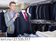 Купить «Seller in business clothes measuring jacket», фото № 27535517, снято 28 сентября 2017 г. (c) Яков Филимонов / Фотобанк Лори