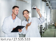 Купить «Man and woman employees on winery manufactory», фото № 27535533, снято 22 июля 2018 г. (c) Яков Филимонов / Фотобанк Лори