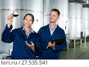 Купить «Man and woman employees on winery manufactory», фото № 27535541, снято 22 июля 2018 г. (c) Яков Филимонов / Фотобанк Лори