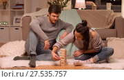 Купить «happy couple playing block-stacking game at home», видеоролик № 27535757, снято 23 января 2018 г. (c) Syda Productions / Фотобанк Лори