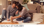 Купить «happy couple playing block-stacking game at home», видеоролик № 27535841, снято 23 января 2018 г. (c) Syda Productions / Фотобанк Лори