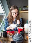 Купить «Young brown-hair woman pours sugar into a her cup», фото № 27536105, снято 24 июля 2017 г. (c) Сергей Дубров / Фотобанк Лори