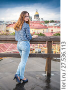 Купить «Leggy long-hair girl wearing blue jeans and blouse stands on the roof of the building in centre of Saint-Petersburg», фото № 27536113, снято 24 июля 2017 г. (c) Сергей Дубров / Фотобанк Лори
