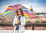 Купить «Brown-hair girl wearing blue jeans, blouse and raincoat with open bright umbrella on the roof of the building», фото № 27536121, снято 24 июля 2017 г. (c) Сергей Дубров / Фотобанк Лори