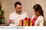 Купить «happy couple with christmas gift at home», видеоролик № 27540421, снято 17 января 2018 г. (c) Syda Productions / Фотобанк Лори