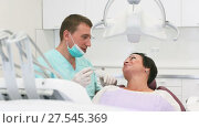 Купить «adult dentist with smiling patient woman sitting in medical Center», видеоролик № 27545369, снято 22 октября 2017 г. (c) Яков Филимонов / Фотобанк Лори