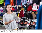 Купить «Female customer examining knit caps in sports store», фото № 27547241, снято 22 ноября 2016 г. (c) Яков Филимонов / Фотобанк Лори