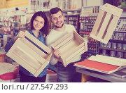 Купить «Young couple demonstrating boxes for decorating house in paint store», фото № 27547293, снято 9 марта 2017 г. (c) Яков Филимонов / Фотобанк Лори