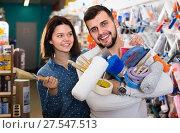 Купить «Young friendly couple demonstrating tools for house renovating in paint store», фото № 27547513, снято 9 марта 2017 г. (c) Яков Филимонов / Фотобанк Лори
