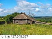Купить «Старый заброшенный деревянный дом и зеленые холмы на заднем плане», фото № 27548357, снято 7 августа 2017 г. (c) Pukhov K / Фотобанк Лори