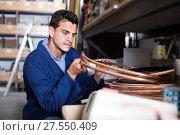 Купить «Salesman in uniform is checking rolls of copper trumpet», фото № 27550409, снято 26 июля 2017 г. (c) Яков Филимонов / Фотобанк Лори