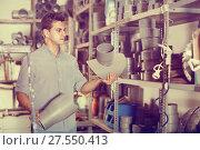 Купить «Male is choosing plastic trumpet in plumbing department», фото № 27550413, снято 26 июля 2017 г. (c) Яков Филимонов / Фотобанк Лори