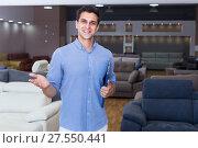 Купить «Seller man is showing prices on sofas», фото № 27550441, снято 19 июня 2017 г. (c) Яков Филимонов / Фотобанк Лори