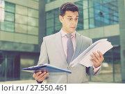 Купить «Dissatisfied businessman holding papers», фото № 27550461, снято 8 мая 2017 г. (c) Яков Филимонов / Фотобанк Лори