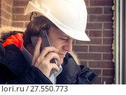Купить «Construction inspector in white helmet talking on mobile phone on the brown brick wall background. Soft focus, toned. Close up.», фото № 27550773, снято 17 июля 2018 г. (c) Marina Sharova / Фотобанк Лори