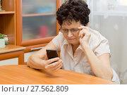 Купить «Пожилая женщина в очках всматривается в экран телефона, пытаясь разглядеть что там написано», фото № 27562809, снято 4 февраля 2018 г. (c) Лариса Капусткина / Фотобанк Лори