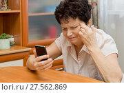 Купить «Пожилая женщина с мобильником щурится и растягивает уголки глаз, пытаясь увидеть информацию на экране телефона», фото № 27562869, снято 4 февраля 2018 г. (c) Лариса Капусткина / Фотобанк Лори