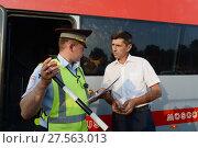 Купить «Инспектор дорожно-патрульной службы полиции проверяет документы у водителя междугороднего пассажирского автобуса», фото № 27563013, снято 3 августа 2017 г. (c) Free Wind / Фотобанк Лори