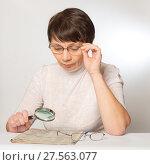 Купить «Проблемы со зрением. Женщина читает газету в очках и с лупой», фото № 27563077, снято 5 февраля 2018 г. (c) Юлия Бабкина / Фотобанк Лори