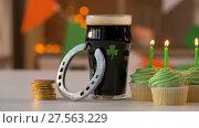 Купить «glass of beer, cupcakes, horseshoe and gold coins», видеоролик № 27563229, снято 1 февраля 2018 г. (c) Syda Productions / Фотобанк Лори