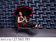 Beautiful sexy asian woman in a small black dress on a chair, modern studio image. Стоковое фото, фотограф Нелли Сабитова / Фотобанк Лори