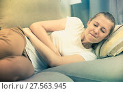 Купить «Girl is lying unhappy because she has a stomach ache», фото № 27563945, снято 4 октября 2017 г. (c) Яков Филимонов / Фотобанк Лори