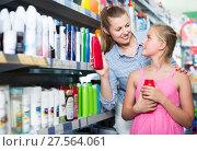 Купить «happy woman with girl choosing shampoo and conditioner», фото № 27564061, снято 5 августа 2017 г. (c) Яков Филимонов / Фотобанк Лори