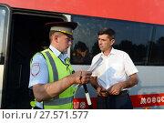 Купить «Инспектор дорожно-патрульной службы полиции проверяет документы у водителя междугороднего пассажирского автобуса», фото № 27571577, снято 3 августа 2017 г. (c) Free Wind / Фотобанк Лори