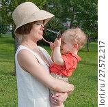 Купить «Молодая женщина в соломенной светлой шляпе держит ребенка на руках и играет с ним. Малыш пытается надеть на маму солнцезащитные очки», фото № 27572217, снято 24 июля 2016 г. (c) Наталья Николаева / Фотобанк Лори