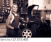Купить «female technician standing with wheel balancing machinery at auto workshop», фото № 27573405, снято 19 сентября 2019 г. (c) Яков Филимонов / Фотобанк Лори