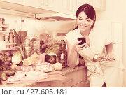Купить «Female is searching new recipe in smartphone on the kitchen», фото № 27605181, снято 23 ноября 2019 г. (c) Яков Филимонов / Фотобанк Лори
