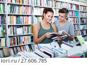 Купить «Two teenagers reading book together in shop», фото № 27606785, снято 16 сентября 2016 г. (c) Яков Филимонов / Фотобанк Лори